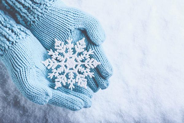 女手在光蓝绿色的针织手套与雪的背景闪闪发光精彩的雪花。冬季和圣诞节的概念(fotolia)