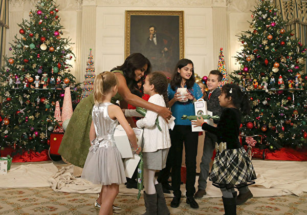 2015年12月02日,華盛頓特區白宮,第一夫人米歇爾·奧巴馬歡迎軍人家屬到白宮參觀聖誕節裝飾展中,擁抱和招呼來參觀的孩童。(Mark Wilson/Getty Images)