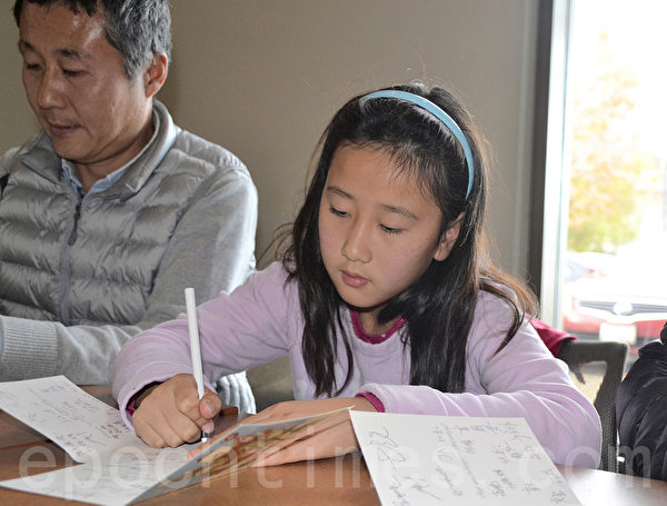 2015年12月13日,小姑娘Selena随父母一起来为狱中良心囚犯写贺卡。(梁博/大纪元)