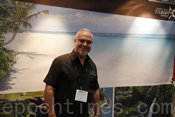 波多黎各旅游公司经理西索在摊位前。(施萍/大纪元)