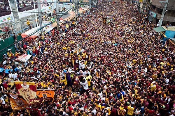 """2016年1月9日,世界上最大的天主教圣会之一的菲律宾""""黑拿撒勒人""""出巡,马尼拉上百万菲律宾男女赤脚搏命靠近,只求""""一亲神泽"""",祈能带来好运。(NOEL CELIS/AFP/Getty Images)"""