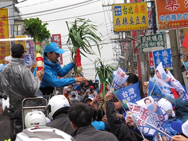 中国国民党总统候选人朱立伦(左2蓝衣)1月13日在桃园车队扫街,民众热情送上菜头、蒜苗、包子等,祝福朱立伦高票当选。(国民党提供)
