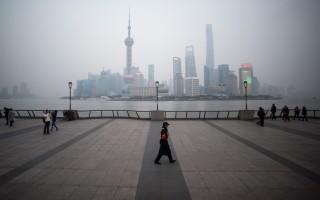 2016年1月18日,中國上海,一名保安走在橫跨浦東新區金融區的黃浦江外灘。(JOHANNES EISELE/AFP)