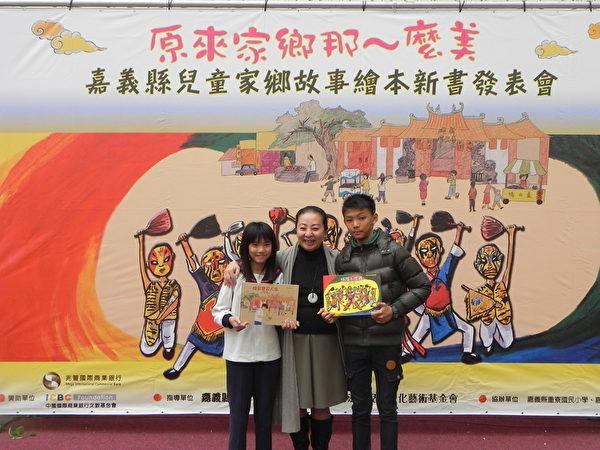 嘉义县重寮国小与月眉国小两所小学的学生代表将《城隍小家将》(右)与《烧出宝石人生》(左)两本故事绘本新书,呈现给县长张花冠(中)。(蔡上海/大纪元)