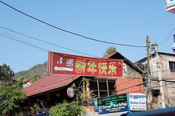突然,出現了標準的漢字!是在一個閃亮的長條紅布上,寫著「新年快樂」,右邊還畫著兩個帶流蘇的紅燈籠。彷彿漢語是尼泊爾的國語。(作者朱瑞提供)