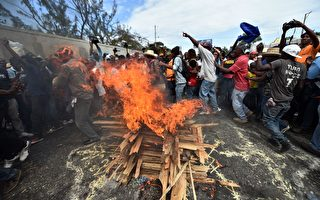 海地选委会于2016年1月22日宣布,为了安全理由,暂停将在24日举行的总统选举。本图为海地反选举的示威民众,在22日上街头进行抗议仪式。(HECTOR RETAMAL/AFP/Getty Images)
