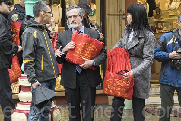 第三区市议员佩斯金和警员向商家派发防罪购物袋。(曹景哲/大纪元)
