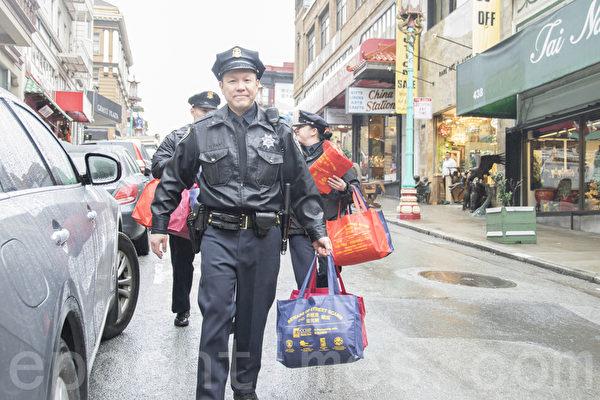 中央警局华裔警员向都板街商家派发防止罪案宣传册及防范祈福党的购物袋。(曹景哲/大纪元)