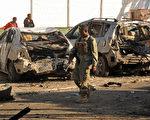 2016年1月22日,一名索马里士兵走过摩加迪沙21晚被恐攻的丽都海鲜餐厅门前,这家餐厅是当地政要常聚集之地。图为被炸毁的汽车。(MOHAMED ABDIWAHAB/AFP/Getty Images)