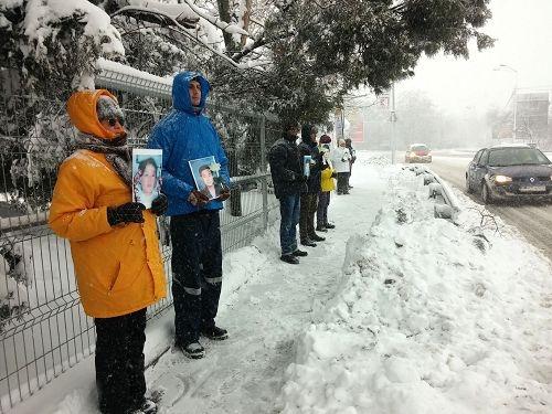 学员们手持被迫害致死的法轮功学员照片,在中使馆前和平抗议(图片来源:明慧网文章《风雪中的坚守》)