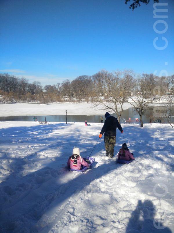 暴風雪過後,大人帶孩子到法拉盛凱辛娜公園滑雪。(林丹/大紀元)