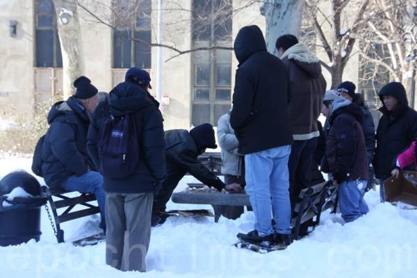 耆老棋友們在雪堆環繞中,興緻勃勃的落子佈局。(蔡溶/大紀元)