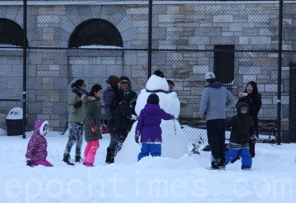 大人帶著孩子們打雪仗、堆雪人。(蔡溶/大紀元)