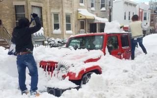 家住7大道56街的郑氏小姐妹,站在雪堆上,清理爱车上的积雪。(杜国辉/大纪元)