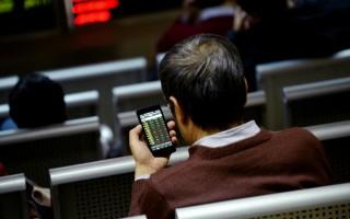 中國互聯網絡信息中心的數據顯示,截至2015年年底為止,中國網民的人數已經超過總人口的一半。圖為一名中國網民用手機上網查看股市行情。(WANG ZHAO/AFP)