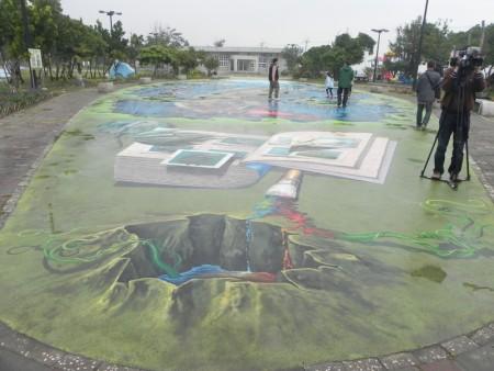 """位于""""好美渔村公园""""的全台最大3D彩绘地画-《抹香鲸大战大王乌贼》是""""好美3D海洋世界""""最吸睛的作品,大人小孩惊奇之余,摆出各种姿势拍照。(蔡上海/大纪元)"""