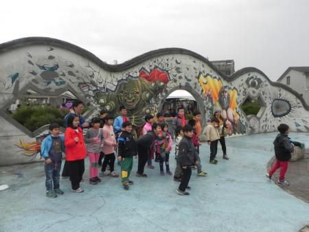 """大小朋友来到""""好美渔村公园""""参观全台最大3D彩绘地画-《抹香鲸大战大王乌贼》,在惊奇之余,摆出各种姿势拍照,好玩又有趣。(蔡上海/大纪元)"""