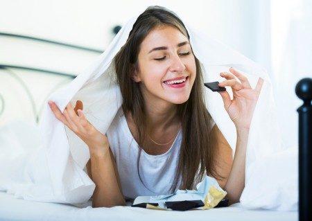 快乐的女孩躲在床上的被窝里开心的吃巧克力.(fotolia)