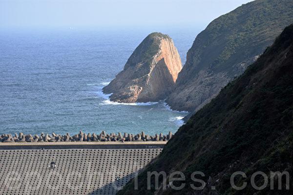 从东坝遥纪念碑望破边洲,隐约可以看到山体被分成两边的海蚀柱。(孙明国/大纪元)