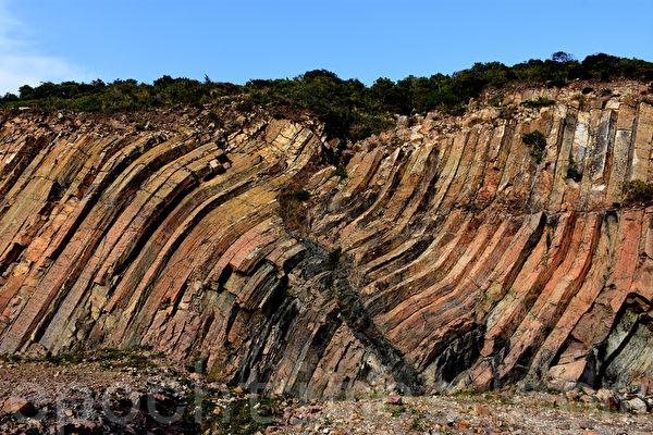 位於東壩下方的地標,彎曲的六角岩柱牆,中間有個人形裂痕,地下岩漿沿著裂縫入侵,冷卻後形成深灰色的侵入岩牆。(孫明國/大紀元)