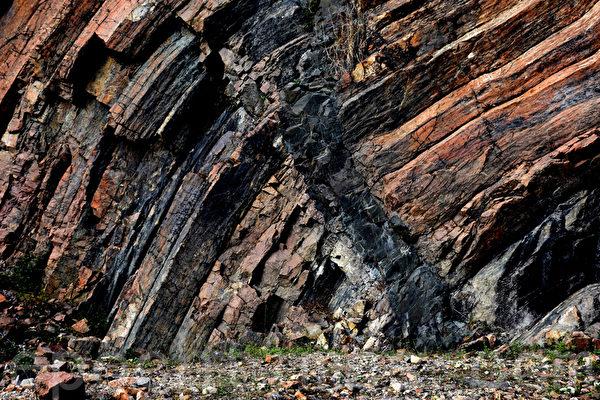 地下岩浆沿着弯曲岩柱的裂缝入侵,冷却后留下一道深灰色的人形痕迹。鬼斧神工的留下一道天然的岩柱石墙壁画。(孙明国/大纪元)