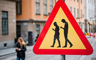 2016年2月2日,在斯德哥爾摩附近的老城區,出現針對專注於智能手機的低頭族行人的警告交通標誌。(JONATHAN NACKSTRAND/AFP)