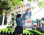 胡志明在泰國大王宮前舉展板向中國遊客講真相。(大紀元)