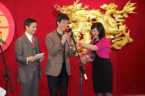 大纪元新年餐会活动主持人给抽中奖品的幸运来宾(中)颁奖。(Félix Boulanger / 大纪元)