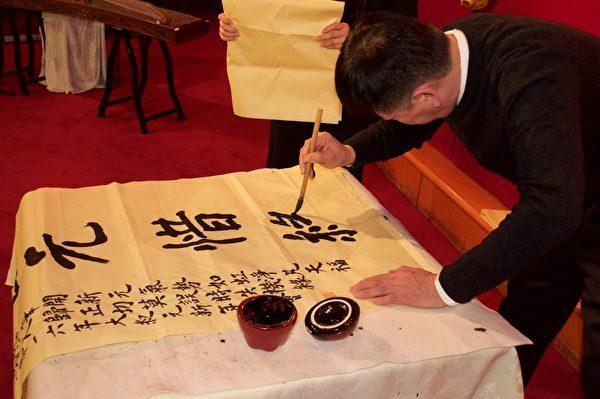 蒙特利尔兰亭汉字社的Jason Sun先生在餐会上挥毫献字,为大纪元新年餐会助兴。(Félix Boulanger / 大纪元)