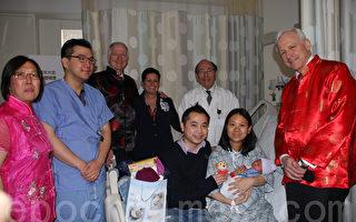 朱万涛(右一)、黎翠文(左一)、妇产科医生胡兆文(Dr. Roland Nyein,左二)、医院行政主任贺文(StevenHermann,左三)、护士主任Mary Greco(左四)及妇产科总监Snyder(白衣者)祝贺新年宝宝的诞生,为小宝宝送上新年利是与礼物。 (蔡溶/大纪元)