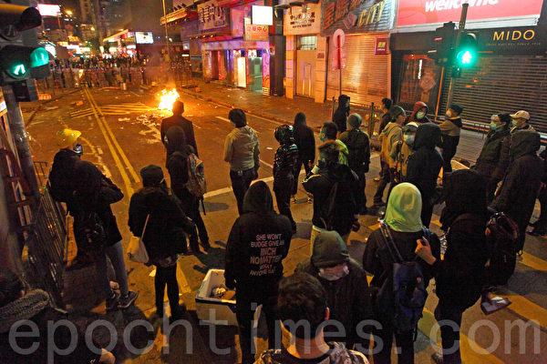 旺角山東街與砵蘭街交界,近凌晨零時爆發警民衝突,警方一度展示紅旗、施放胡椒噴霧,並向示威者揮動警棍控制場面,有示威者向警員投擲雜物。其間有警員向後退時倒地受傷,警方向天開2槍警告。(潘在殊/大紀元)