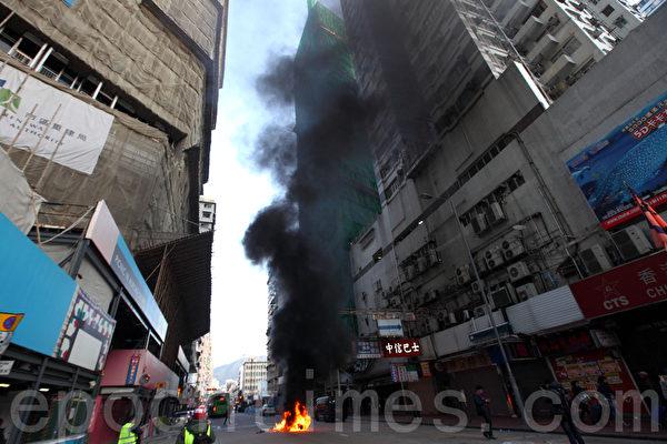 旺角山東街與砵蘭街交界,大年初一近凌晨零時爆發警民衝突,警方一度展示紅旗、施放胡椒噴霧,並向示威者揮動警棍控制場面,有示威者向警員投擲雜物。其間有警員向後退時倒地受傷,警方向天開2槍警告,示威者之後多處放火。(潘在殊/大紀元)