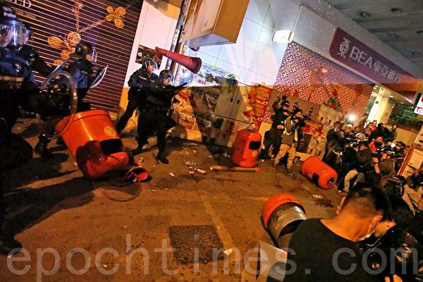 旺角山東街與砵蘭街交界,大年初一近凌晨零時爆發警民衝突,警方一度展示紅旗、施放胡椒噴霧,並向示威者揮動警棍控制場面,有示威者向警員投擲雜物。(潘在殊/大紀元)