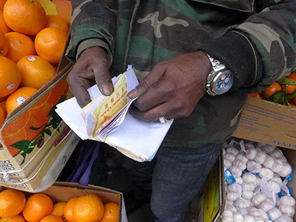 乌拉手上拿着厚厚一叠送货单,无奈的说,他被扫荡的蔬果约有126箱,价值约8,300元。 (蔡溶/大纪元)