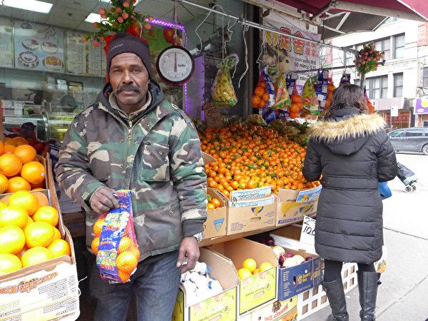 摊主乌拉说,小摊贩生意薄利多销,他手上这袋橘子只卖5元,利润1毛5分。(蔡溶/大纪元)