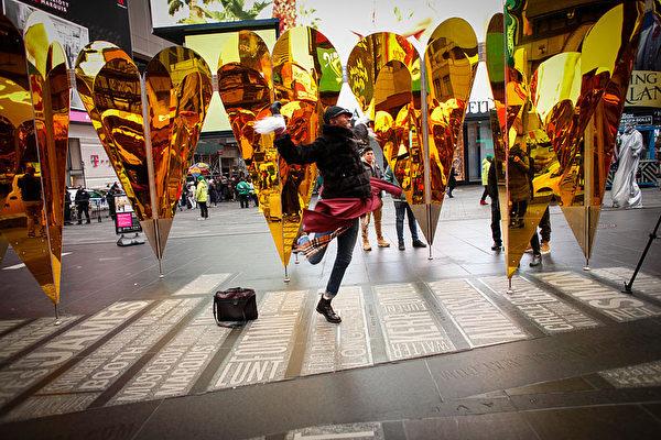 一人在時代廣場的情人節裝置藝術前歌舞。(KENA BETANCUR/AFP/Getty Images)