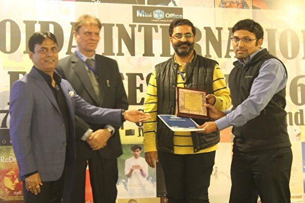 新唐人電視臺兒童動畫《天庭小子-小乾坤》,榮獲印度最大電影節之一的印度諾伊達國際電影節(3rd Noida International Film Festival-2016)的「最佳動畫片-評審團獎」。圖為新唐人代表接受獎牌。(新唐人亞太電視臺)