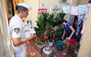 圖為巴西海軍水手檢查一名婦女的家,並宣傳如何保護避免被蚊子叮咬。(Mario Tama/Getty Images)