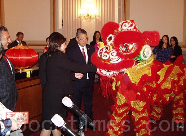 """2月10日晚,在美国国会Cannon办公楼内""""首届国会新年欢庆和招待会""""上,多位国会议员到场,并给狮子喂红包,祝福新年吉祥。(林帆/大纪元)"""