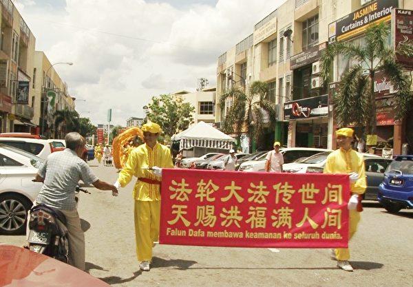 老居民在路旁向隊伍握手致意。(新唐人視頻截圖)