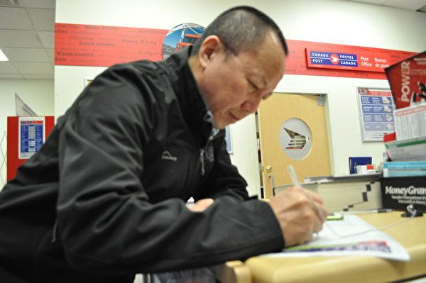 李建峰在温哥华邮局填写投递到中共高检的信件地址,加入控告江泽民的大潮中。(唐风/大纪元)