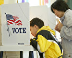 """LOS ANGELES, UNITED STATES:  Eight-year-old David Luu helps his mother Hui Zhang, a Cantonese speaker, read and complete her ballot at a polling center set up inside a community center in Chinatown in Los Angeles, California, 02 March 2004. California residents are voting in the """"Super Tuesday"""" primary for the Democratic presidential nominee who will run against George W. Bush in the presidential election, as well as voting on California state budget propositions 57 and 58.  AFP PHOTO / Robyn BECK  (Photo credit should read ROBYN BECK/AFP/Getty Images)"""