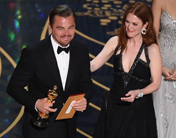四度入围奥斯卡影帝的莱昂纳多‧迪卡普里奥凭借《荒野猎人》最终捧得小金人。右为颁奖嘉宾——上届影后朱莉安‧摩尔。(MARK RALSTON/AFP/Getty Images)