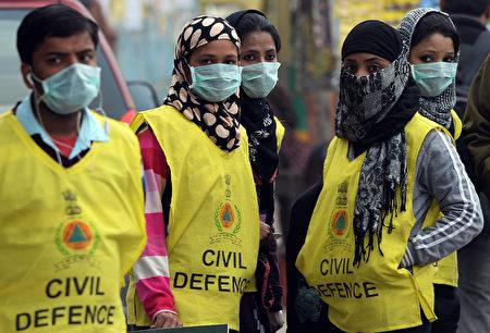 戴口罩的印度新德里民防志工,至1月15日他们监测了超过3000人的肺活量。测试显示,有超过1/3的受测者肺活量低于70%,显示肺功能受损。(PRAKASH SINGH / AFP /Getty)