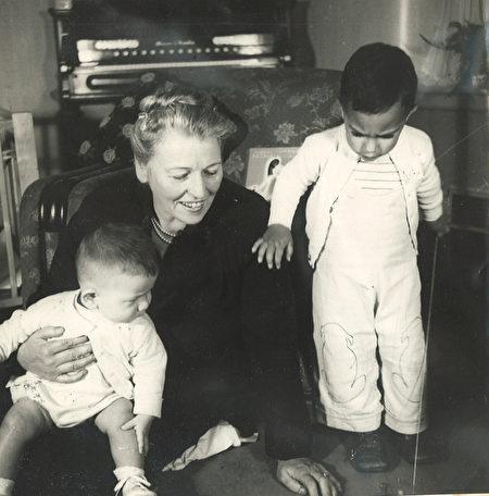 赛珍珠正在给莱昂Leon(坐着)和欢迎之家的第一个收助的孩子大卫David(站着)读书。(赛珍珠国际组织提供)