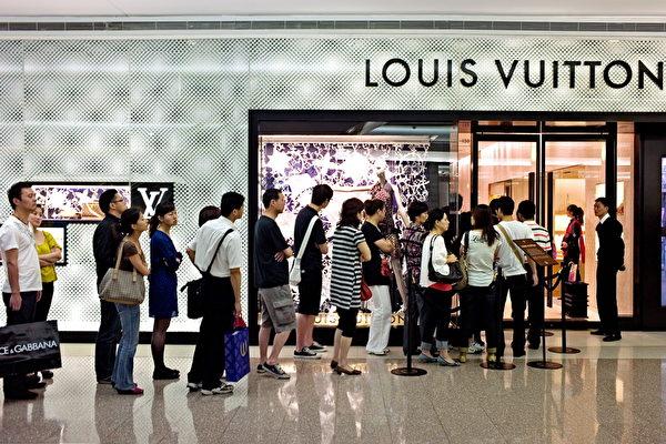 由于中国制假货充斥,中国消费者透过在美国、日本、法国、韩国等国家的中间人购买高档真品。图为法国奢侈品店外排队的中国人。(PHILIPPE LOPEZ/AFP/Getty Images)