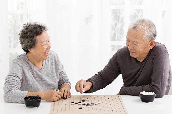 在客廳裡快樂的亞洲老年夫婦在下湖圍棋。(fotolia)