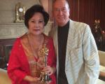 华裔制片人杨华沙与《雨人》编剧巴瑞‧莫若(Barry Morrow)和其获奖小金人合影。(杨华沙提供)