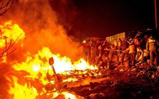 法國當局3月1日繼續拆除位於加萊外緣名為「叢林」的簡陋難民營地,警方動用了催淚瓦斯。圖為難民和志願者試圖撲滅將棚屋夷為平地的大火。(PHILIPPE HUGUEN/AFP/Getty Images)