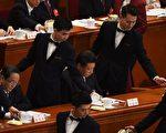 今年3月5日中共人大開幕會議上,為常委們倒茶的男服務員。(Photo credit should read GREG BAKER/AFP/Getty Images)